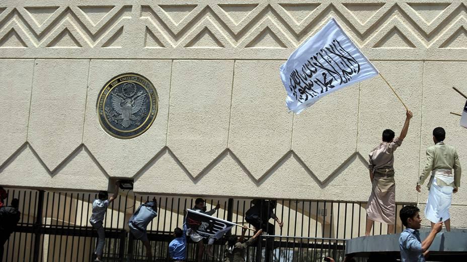 """Manifestantes seguram uma bandeira com os dizeres """"O único Deus é Alá e seu profeta é Maomé"""" durante protesto na embaixada americana em Sana, no Iêmen"""