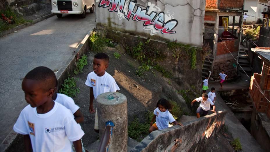 Crianças a caminho do ponto de leitura da comunidade Caracol, complexo da Penha, no Rio de Janeiro