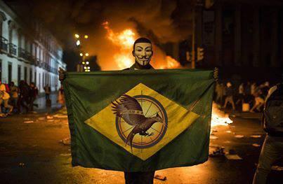 Manifestante exibe bandeira brasileira com o símbolo da saga Jogos Vorazes no centro, em protestos no Brasil