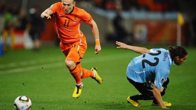 Arjen Robben passa pela marcação de Martin Caceres durante partida entre Holanda e Uruguai pelas Semifinais da Copa da África do Sul