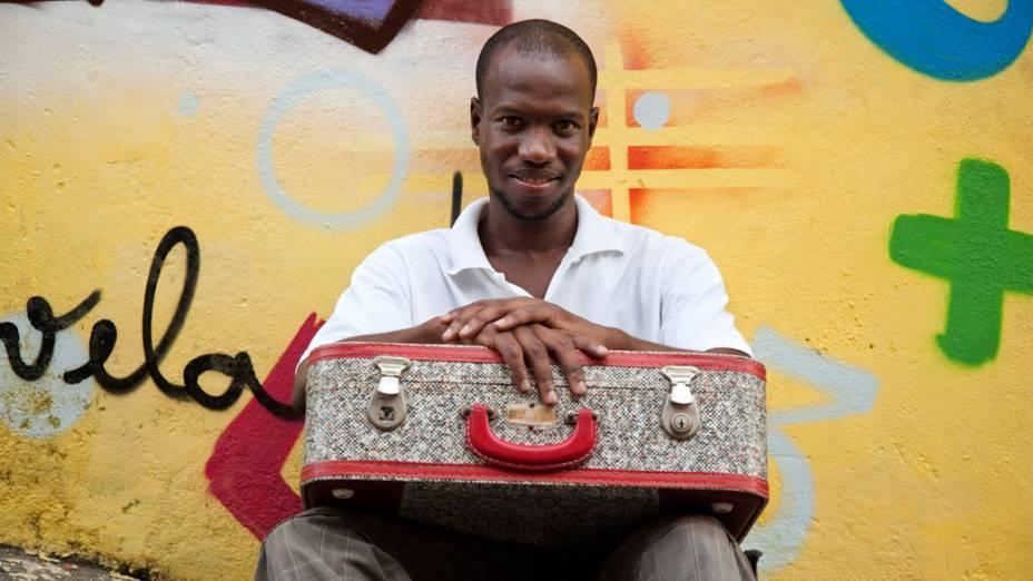 Otávio Cesar Santiago de Souza Junior, promotor de leitura do projeto Ler é Dez Leia Favela, posa em frente ao ponto de leitura com a mala encontrada no lixo e que foi utilizada inicialmente para transportar seus livros pelo complexo da Penha, no Rio de Janeiro