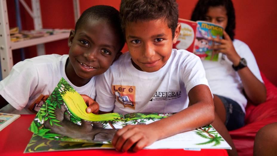 Crianças no ponto de leitura da comunidade Caracol, complexo da Penha, no Rio de Janeiro