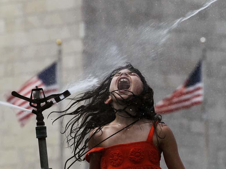 Menina se refresca em Washington, nos Estados Unidos, onde os termômetros marcaram 37°C