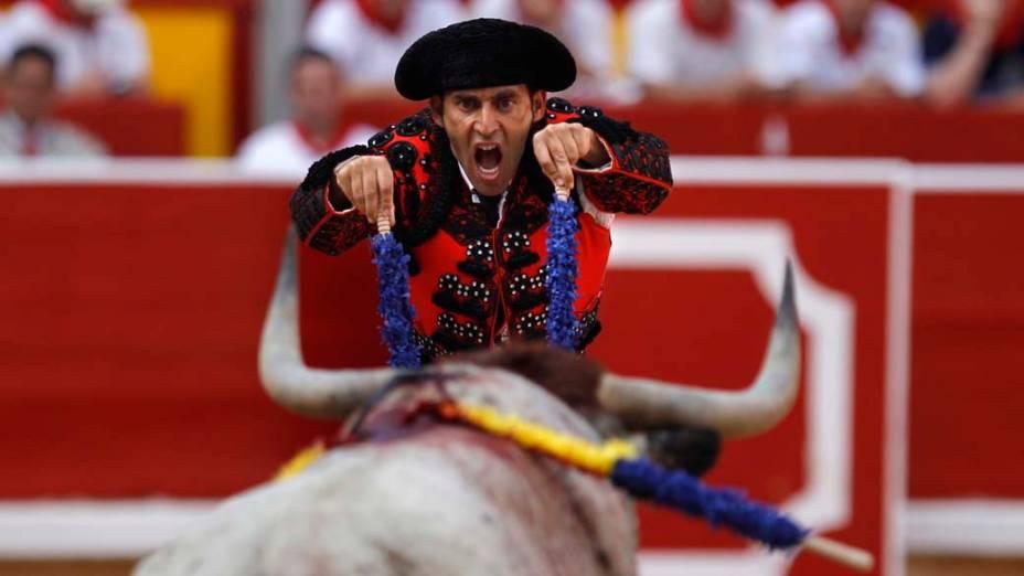 """Um assistente de toureiro espeta um par de """"banderillas"""" em um animal em Penajara, durante a primeira tourada das festividades espanholas de San Fermin"""