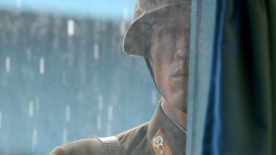Soldado norte-coreano olha através de uma janela do edifício das Organizações da Nações Unidas (ONU) na zona desmilitarizada (faixa que divide as duas Coreias). A secretária de Estado dos Estados Unidos, Hillary Clinton, e o secretário de Defesa, Robert Gates, realizaram nesta quarta-feira uma visita inédita e simbólica à fronteira entre as duas Coreias para demonstrar apoio a Seul