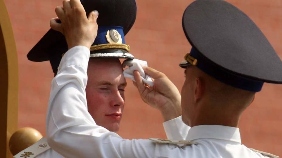 Soldado limpa o suou do rosto do colega, em Moscou. As temperaturas na Rússia ultrapassaram os 35ºC