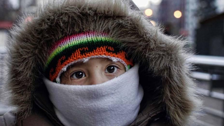 Criança se protege do frio em Santiago, no Chile. O país enfrenta o pior inverno dos últimos três anos
