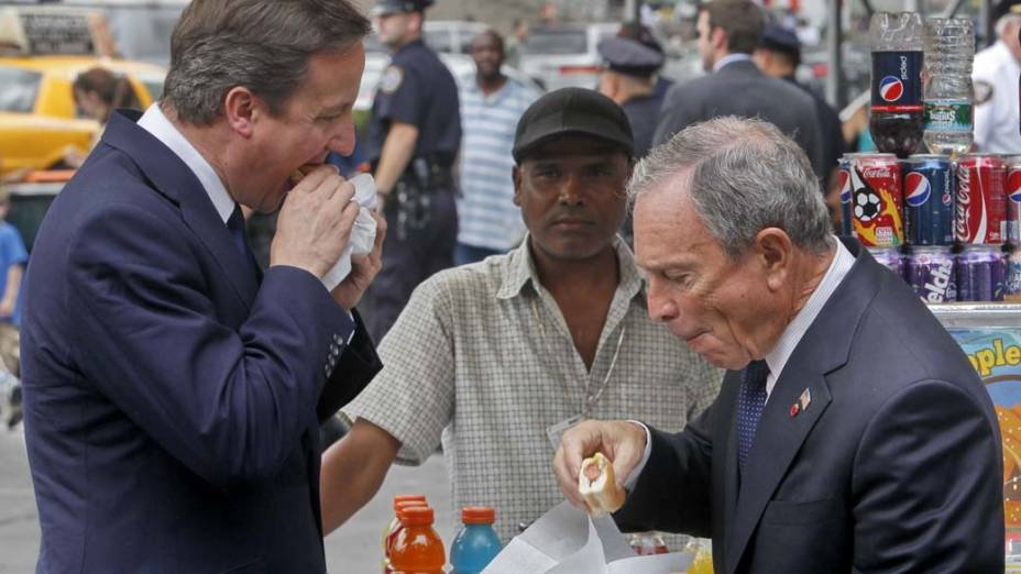 O primeiro-ministro britânico, David Cameron, e o prefeito de Nova York, Michael Bloomberg, comem cachorros-quente durante a primeira visita do britânico aos Estados Unidos
