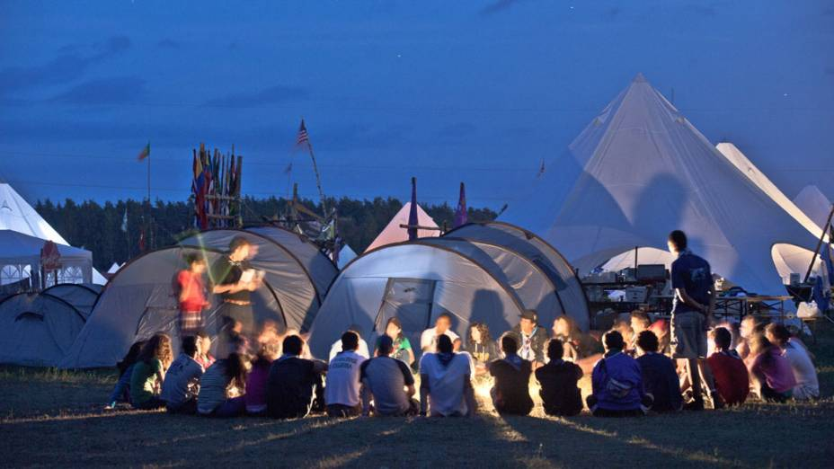 Escoteiros reúnem-se em torno de uma fogueira, durante o 22º Acampamento Mundial Escoteiro
