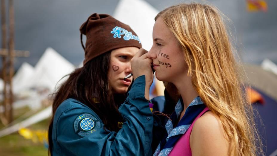 """Jovens escoteiras pintam o rosto com a mensagem """"Free Hugs"""" (Abraço Grátis), durante o 22º Acampamento Mundial Escoteiro"""