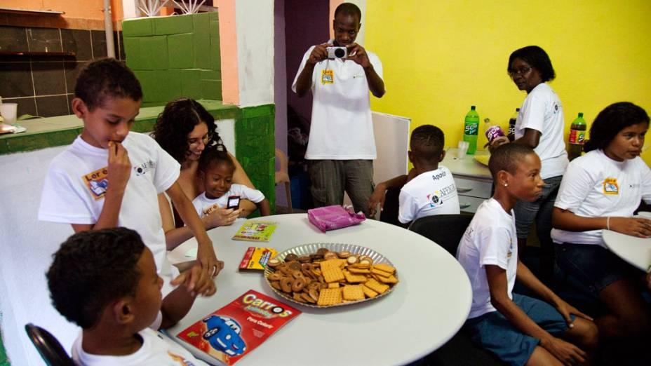 Otávio Cesar e crianças no ponto de leitura da comunidade Caracol, complexo da Penha, no Rio de Janeiro