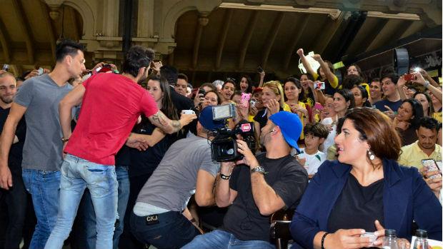 Gusttavo Lima entrega xícara para fã durante show no Mercadão