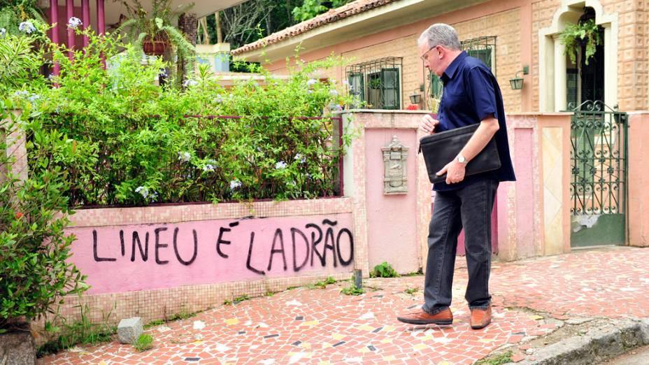 """Lineu ( Marco Nanini ) passa em frente ao muro da casa, onde está pichado: """"Lineu é ladrão"""""""