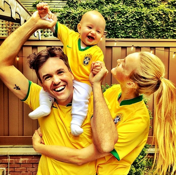 A modelo Carol Trentini, o marido e o filho deles posam vestidos com o uniforme da Seleção Brasileira.