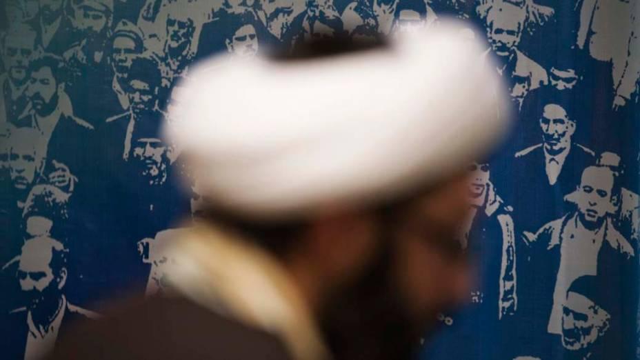 Abdolreza Tarzi está na frente de um banner durante o seu registro como candidato para as eleições parlamentares do Irã, em Teerã