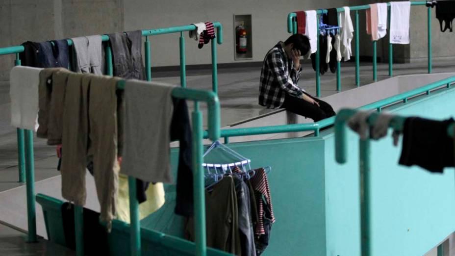 Homem em um ginásio usado como abrigo na cidade de Yamagata, Japão