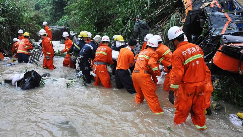 Equipe de resgate retira corpo de vítima de acidente de ônibus na China; 17 morreram após veículo cair em um barranco