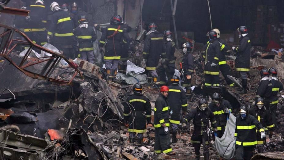 Bombeiros trabalham no resgate de vítimas do acidente com o avião Airbus A-320, da TAM, que se chocou contra um prédio da empresa