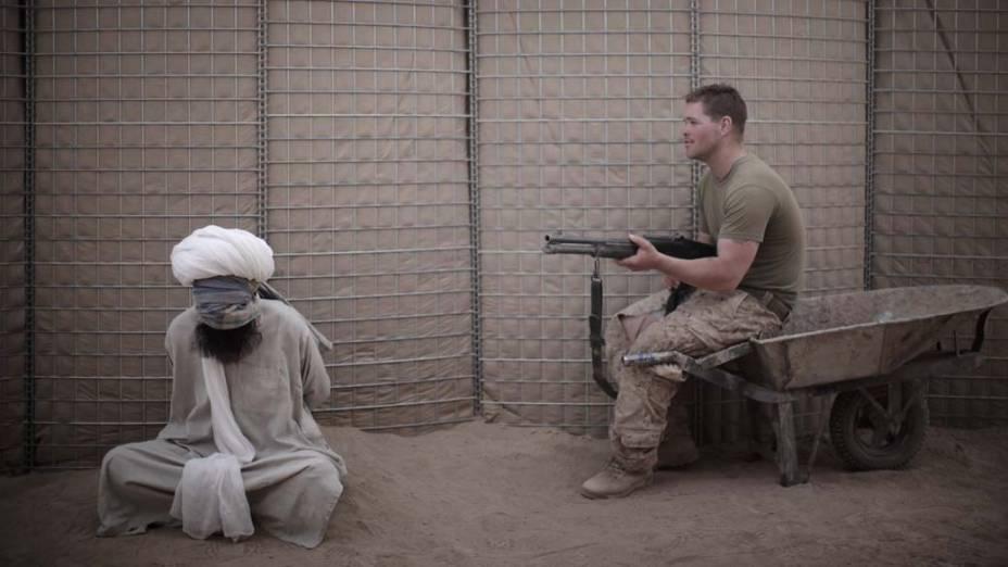 Militar americano vigia afegão preso na província de Helmand, em abril