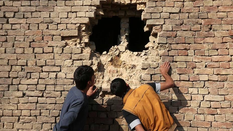 Afegãos olham um buraco na parede de uma casa causado por um foguete de ataque em Cabul