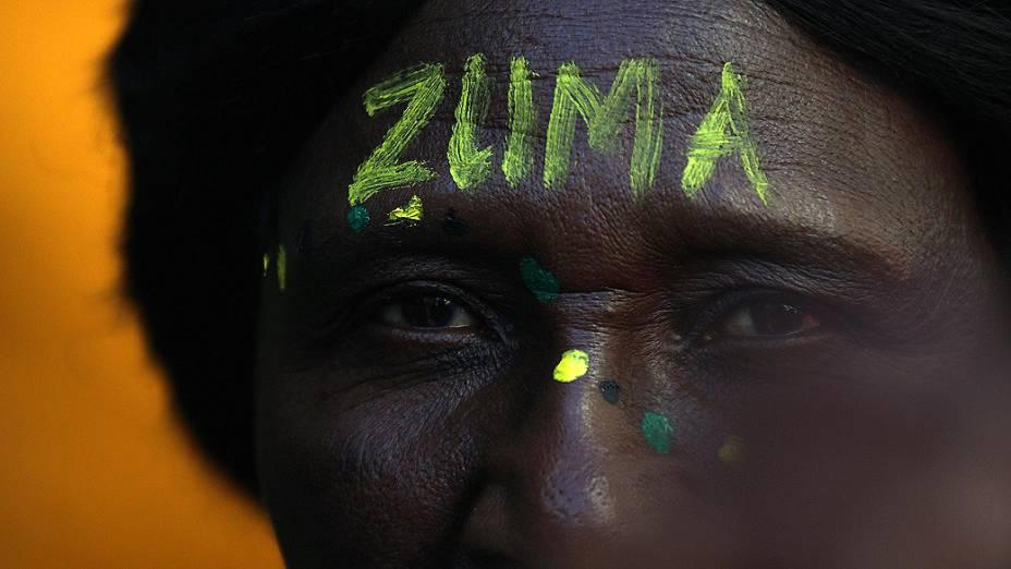 Partidário com a testa pintada, escrito o nome do Presidente Jacob Zuma fora do Tribunal Gauteng South High em Joanesburgo, África do Sul
