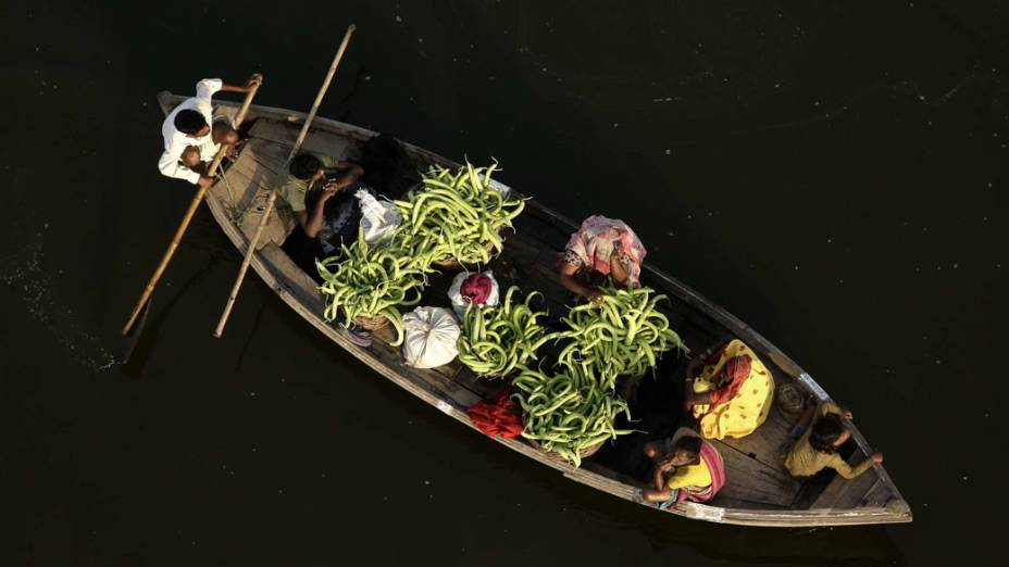 Agricultores indianos usam barco para o transporte de pepinos até o mercado em Allahabad