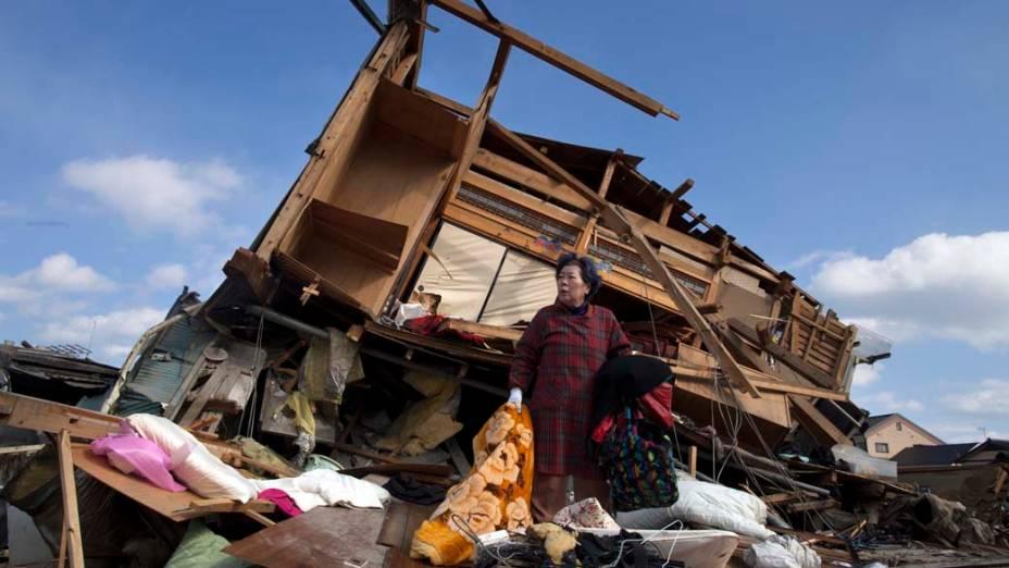 Aiko Musashi se surpreende ao olhar a destruição da casa de seu vizinho enquanto recolhe seus pertences pessoais na cidade de Kesennuma, Japão