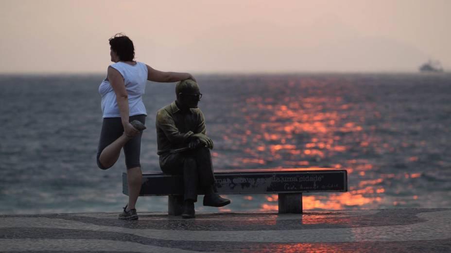 Mulher se apóia na estátua de Carlos Drummond de Andrade durante alongamento em Copacabana, Rio de Janeiro