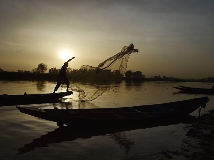 Homem pesca na margem do rio Niger, em Niamey, nesta tarde (21)