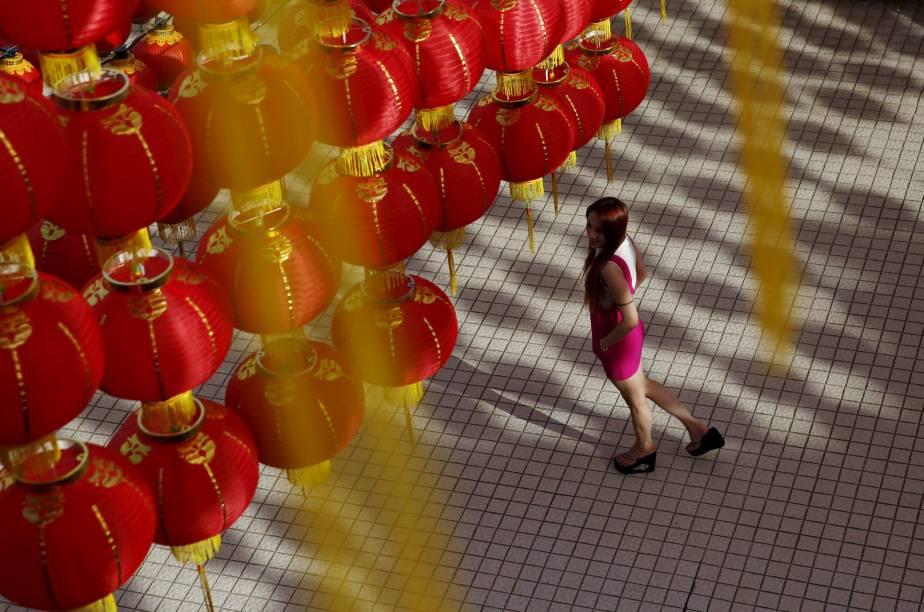 Mulher caminha sob lanternas chinesas que formam a decoração para a celebração do Ano Novo Chinês em Kuala Lumpur, capital da Malásia. Pelo calendário, que é seguido por diversas nações do oriente que têm grande população originária da China, o ano 2130 terá início no próximo dia 8 de fevereiro
