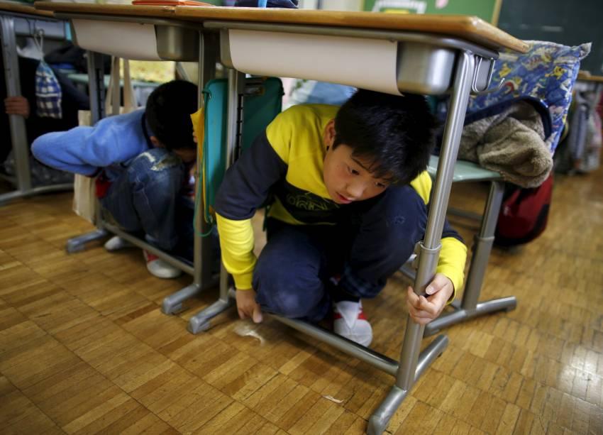 Crianças em idade escolar se protegem embaixo de mesas durante um exercício de simulação de terremoto em uma escola de Tóquio, no Japão, para marcar o aniversário do terremoto e tsunami de 2011 que matou milhares de pessoas e desencadeou uma crise nuclear