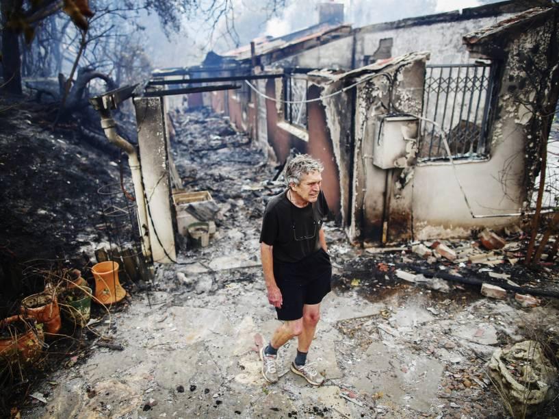 Homem observa os restos de sua casa que foi queimada em um incêndio em Tokai, Cidade do Cabo (África do Sul) - 04/03/2015