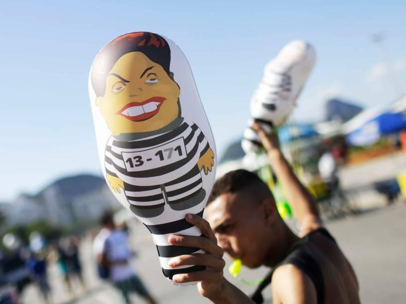 """Homem faz propaganda dos """"pixulecos"""", bonecos infláveis com a imagem da Presidente Dilma. Em Copacabana, manifestantes se reúnem para protestar a favor do Impeachment, no Rio de Janeiro - 17/04/2016"""