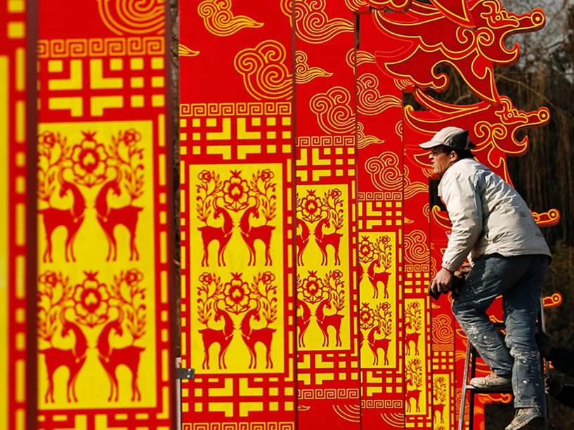 Homem instala decorações para as celebrações do Ano Novo Lunar no parque Taorating, em Pequim, na China