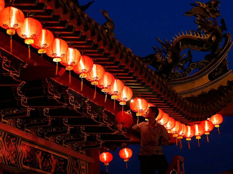Homem faz últimos ajustes em lâmpadas para as celebrações do Ano Novo Chinês, no templo de Thean Hou