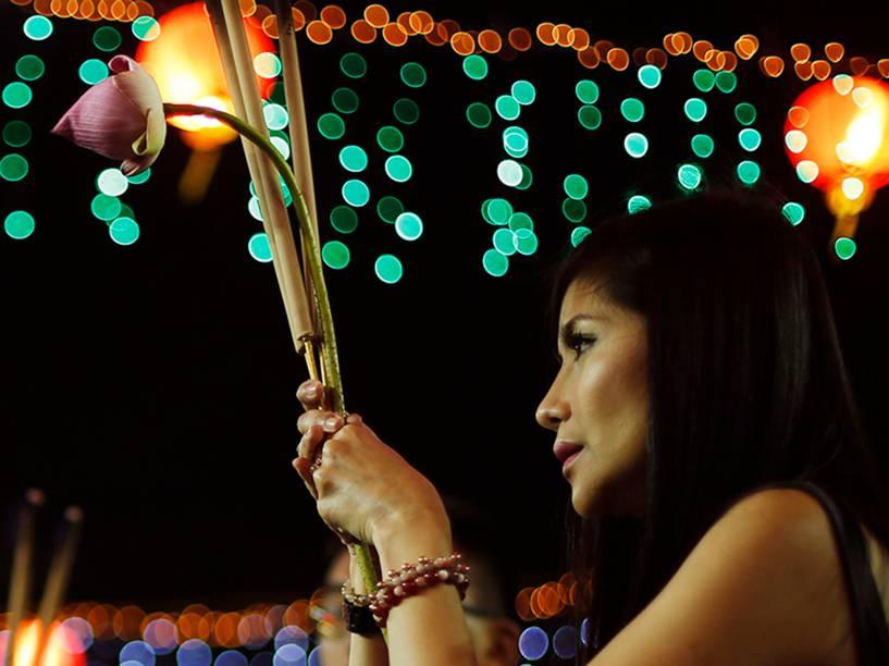 Mulher reza com varas no templo de Kwan Im Thong, em Cingapura. Todos os anos, centenas de pessoas competem para ser o primeiro a colocar incenso em uma urna no templo