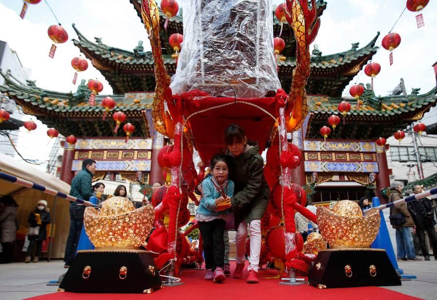 Em Chinatown, sul de Tóquio, mulher e menina caminham através de um santuário chinês em comemoração ao ano do Carneiro