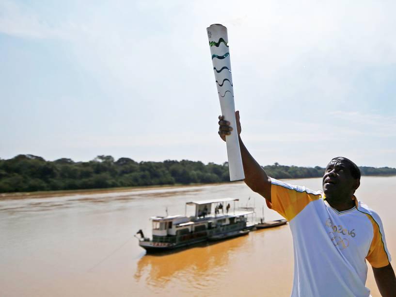 O jogador de futebol Luiz Henrique, do Botafogo-RJ, carrega a tocha olímpica na margem do Rio São Francisco, na cidade de Pirapora (MG) - 09/05/2016