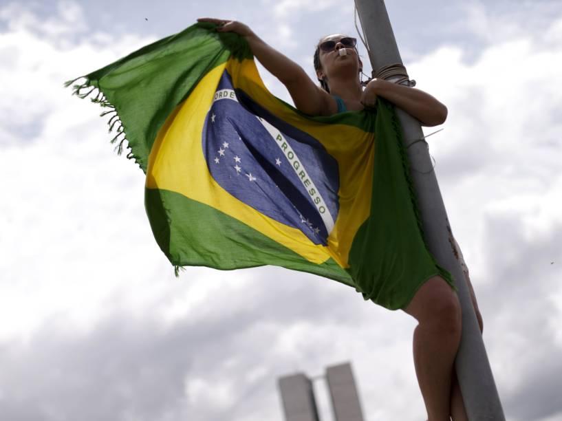 Manifestante segura uma bandeira do Brasil durante protesto pedindo o impeachment da presidente Dilma Rousseff, nos arredores do Congresso Nacional, em Brasília (DF) - 13/12/2015