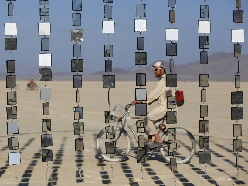"""Homem passa de bibicleta por uma instalação artística durante o """"Burning Man 2015 - Carnaval de Espelhos"""", festival de música e arte que acontece no deserto de Black Rock, Nevada. Cerca de 70.000 pessoas de todo o mundo se reúnem para passar a semana no deserto durante o festival"""