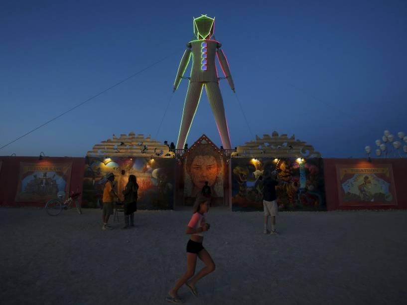 """Escultura de madeira que dá nome ao festival é iluminada ao anoitecer durante o """"Burning Man 2015: Carnaval de Espelhos"""". Cerca de 70.000 pessoas de todo o mundo se reúnem para passar a semana no deserto de Nevada durante o festival"""