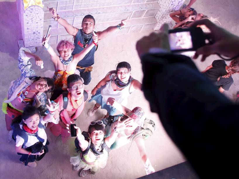 """Grupo de participantes fotografa aos pés da escultura de madeira que dá nome ao festival """"Burning Man 2015: Carnaval de Espelhos"""". A festa tradicional é marcada por música e arte, e acontece no deserto de Black Rock, Nevada"""