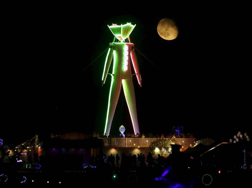 """Lua é vista atrás da escultura de madeira que dá nome ao festival durante o """"Burning Man 2015: Carnaval de Espelhos"""". A festa tradicional é marcada por música e arte, e acontece no deserto de Black Rock, Nevada"""