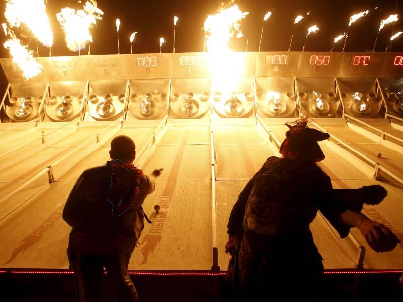 """Pessoas participam de um jogo de skee-ball em chamas durante o """"Burning Man 2015: Carnaval de Espelhos"""". Cerca de 70.000 pessoas de todo o mundo se reúnem para passar a semana no deserto de Nevada durante o festival"""