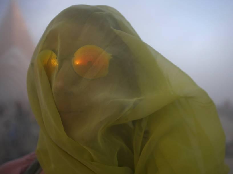 """Mulher cobre o rosto com um lenço para se proteger de uma tempestade de areia durante o """"Burning Man 2015: Carnaval de Espelhos"""". Cerca de 70.000 pessoas de todo o mundo se reúnem para passar a semana no deserto de Nevada durante o festival"""
