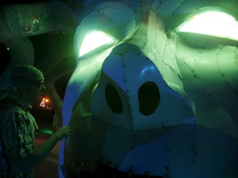 """Participante interage com instalação artística representando Medusa em meio ao """"Burning Man 2015: Carnaval de Espelhos"""". A festa tradicional é marcada por música e arte, e acontece no deserto de Black Rock, Nevada"""