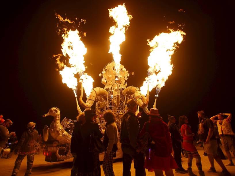"""Participantes se juntam para observar as chamas que saem do veículo artístico """"El Popo Mechanico"""" durante o """"Burning Man 2015: Carnaval de Espelhos"""". A festa tradicional é marcada por música e arte, e acontece no deserto de Black Rock, Nevada"""