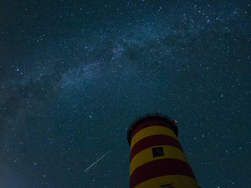 Uma estrela cadente cruza o céu atrás do farol em Pilsum, noroeste da Alemanha, durante o pico da atividade da chuva anual de meteoros Perseidas - 13/08/2015