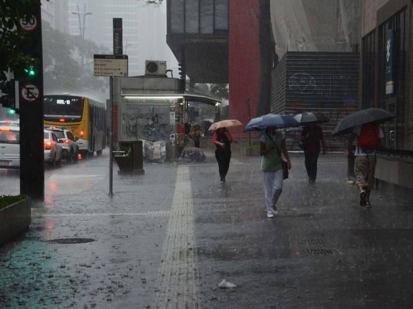 Pedestres se protegem da chuva na Av. Paulista, região central de São Paulo, na tarde desta quarta-feira (25)