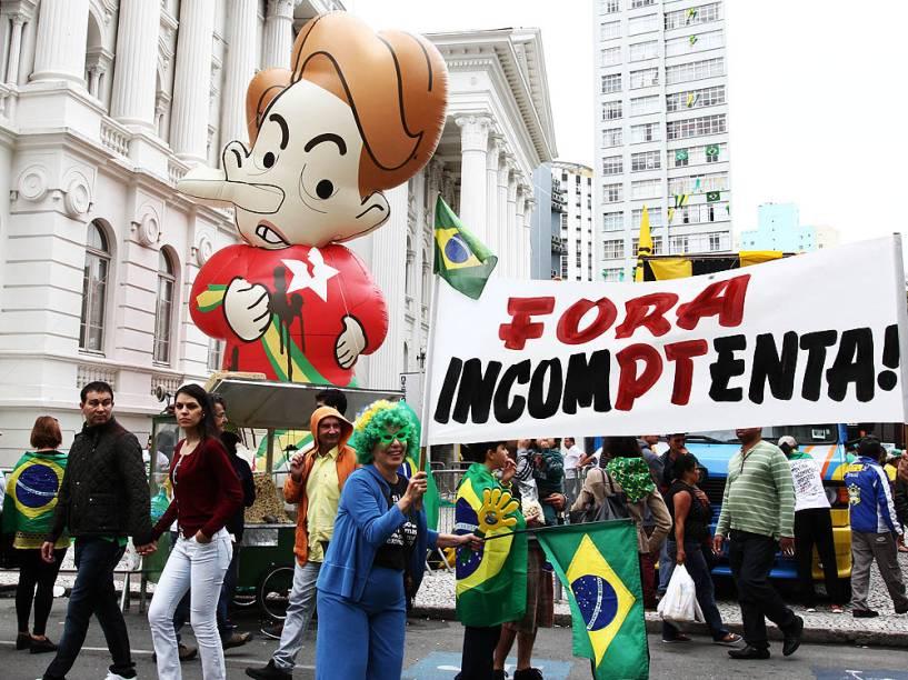 Manifestantes contrários ao governo Dilma Rousseff inflam boneco da presidente durante ato pelo impeachment na Praça Santos Andrade, em Curitiba (PR), neste domingo (13)